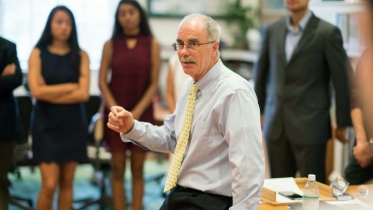 President Hanlon in his office speaking to a group of students.