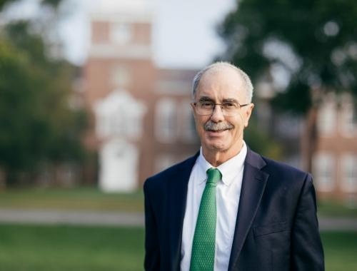 President Hanlon standing in front of Baker Tower.