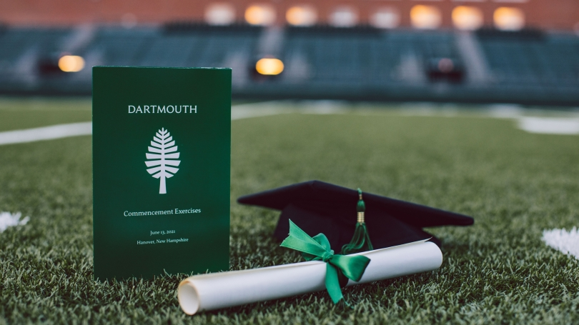 Commencement program, diploma rolled up with a green ribbon, and a mortarboard on the turf of Memorial Field