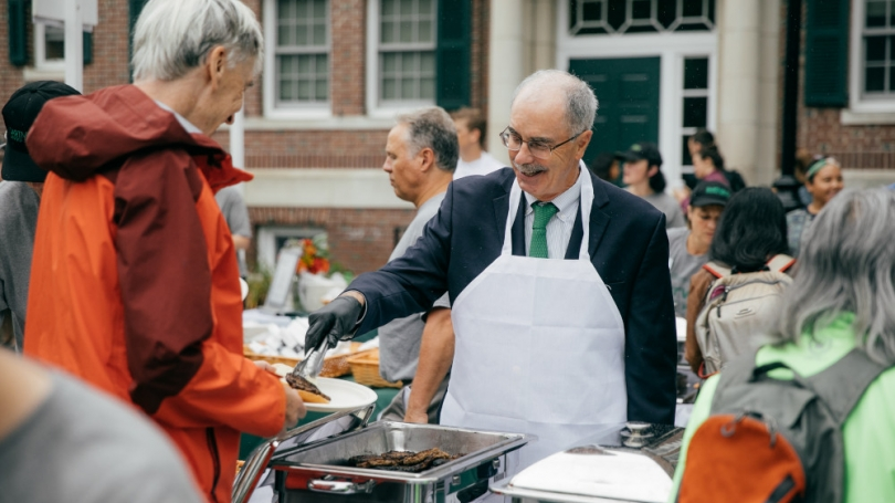 President Hanlon helps serve food during a community lunch.