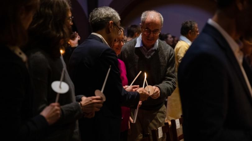 President Hanlong lighting a candle during the MLK Multifaith Celebration.